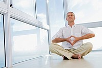 Senior man sitting, doing Yoga exercise, indoors (thumbnail)