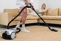 Senior couple, man vacuuming at home, woman lying on sofa