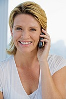 Mature woman smiling while using Cell phone, looking straight at camera