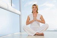 Senior woman sitting, doing Yoga exercise, indoors (thumbnail)