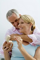 Mature couple hugging and smiling, woman receiving diamond ring