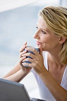 Mature woman at computer, holding cup of coffee
