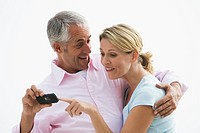 Mature couple laughing while looking at photos on camera phone