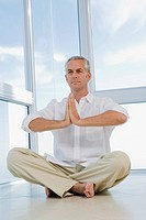 Senior man sitting, doing Yoga exercise, indoors
