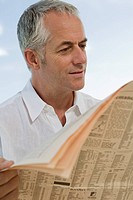 Mature man reading financial newspaper
