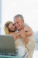 Senior couple hugging and laughing, working with Laptop computer