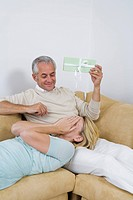 Mature couple on sofa, man holding green present, woman with hands covering eyes
