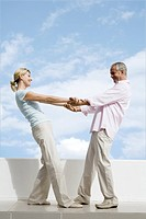 Mature couple standing on terrace holding hands