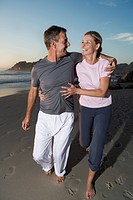 Senior couple laughing while jogging along beach at sunset