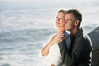 Mature couple sitting on rocks, embracing and enjoying view of coastline