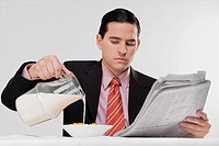 Businessman pouring milk into a bowl of cereal