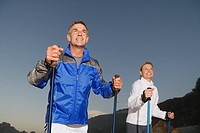Senior couple wearing tracksuit doing Nordic Walking at sunset