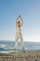 Mature woman standing on cliff, arms raised above her head doing Yoga exercises