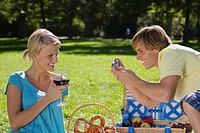 Young couple having picnic, man taking photograph of woman