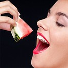 Woman eating a watermelon slice and smiling