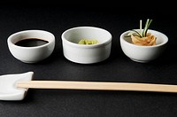 Close_up of chopsticks with soy sauce with wasabi paste and pickled ginger