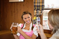 Man taking photo of girl holding beer Mass at Oktoberfest, Munich, Germany