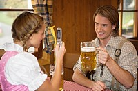 Young woman taking photo of man with cell phone at Oktoberfest, Munich, Germany