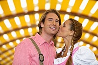 Young couple kissing in beer tent at Oktoberfest, Munich, Germany