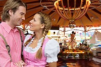 Young couple in front of fairground ride at Oktoberfest, Munich, Germany