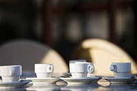 Several white coffee cups and saucers on cafe table, Paris, France
