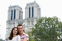 Young couple standing in front of Notre Dame Cathedral, Paris, France