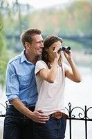 Young couple at riverbank, woman looking through binoculars, Paris, France