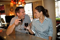 Young couple laughing and drinking red wine in cafe, Paris, France