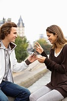 Young couple sitting on bridge, man giving present of miniature Eiffel Tower