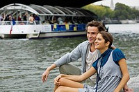 Young couple sitting by river Seine watching tourist boats, Paris France
