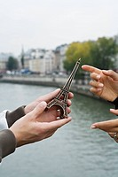 Close up of young man giving present of miniature Eiffel Tower to woman