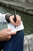Close up of young man writing postcard, Pont Neuf bridge, Paris, France