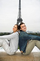 Young couple sitting back to back with Eiffel tower in background, Paris, France (thumbnail)