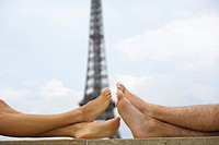 Close up of young couples bare legs with Eiffel tower in background