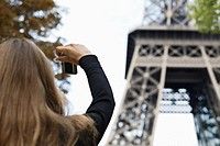 Young woman taking picture of Eiffel Tower, Paris, France