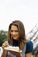 Young woman eating cream covered Waffle in front of Eiffel Tower, Paris, France