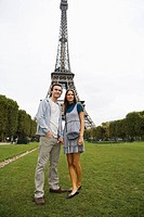 Young couple standing in park with Eiffel tower in background, Paris, France