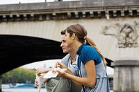 Young couple sitting on steps by river Seine eating snack, Paris, France