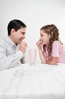 Man and his daughter sharing a milkshake