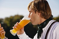 Young man in traditional Bavarian outfit, drinking wheat beer, side profile