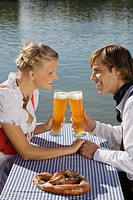 Young couple in traditional Bavarian outfit, sitting in beer garden, Munich,
