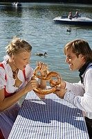 Young couple in traditional Bavarian outfit, fighting over Pretzel, Munich