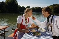 Young couple in traditional Bavarian outfit, sharing meal in beer garden, Munich (thumbnail)