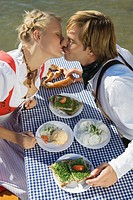 Young couple in traditional Bavarian outfit, kissing in beer garden, Munich