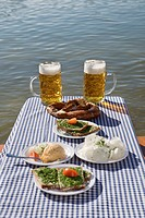 Traditional Bavarian meal on table with beer in beer garden, Munich, Germany