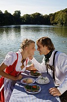 Young couple in traditional Bavarian outfit, caressing in beer garden, Munich