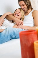 Young couple lying on sofa (thumbnail)