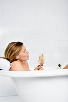 Woman listening to mp3 player in the bath (thumbnail)