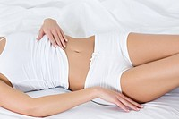 Women on bed touching her stomach