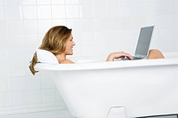 Woman using laptop in the bath